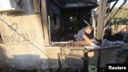 Một sĩ quan cảnh sát Israel kiểm tra ngôi nhà bị hư hỏng nặng sau cuộc tấn công bị nghi ngờ bởi những kẻ cực đoan Do Thái thực hiện ở làng Kafr Duma gần thành phố Bờ Tây Nablus ngày 31/7/2015.