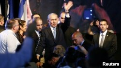 Israeli Prime Minister Benjamin Netanyahu, center, waves to supporters at party headquarters in Tel Aviv, March 18, 2015. (REUTERS/Amir Cohen)