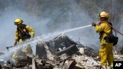 Anggota regu pemadam kebakaran tengah berupaya memadamkan api kebakaran hutan di Lower Lake, California (15/8).