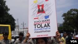 Seorang aktivis berunjuk rasa di depan Istana Merdeka dalam aksi 100 hari Presiden Jokowi, Rabu, 28 Januari 2015. (Foto: VOA/Andylala)