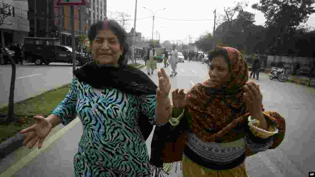 Pakistani women run following an apparent suicide bombing in Lahore, Pakistan, Tuesday, Feb. 17, 2015.