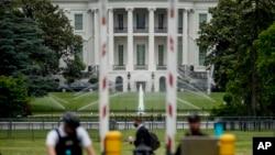 Gedung Putih tampak di belakang sementara paspampres berjaga di pos pemeriksaan di Constitution Avenue, Washington DC, 2 Juni 2020. (Foto: AP)