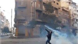 یک معترض به سوی نیروهای امنیتی در حمص گاز اشک آور پرتاب می کند. سوریه ۶ دی ماه ۱۳۹۰ (۲۷ دسامبر ۲۰۱۱)