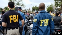 FILE - FBI agents look on as the gay pride parade kicks off in West Hollywood, Calif., June 12, 2016.