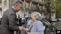 Montenegro's ruling coalition of longtime leader Milo Djukanovic, left, talks to a supporter in front of the polling station in downtown Podgorica, Montenegro, Sunday, Oct. 14, 2012.