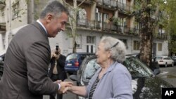 FILE - Montenegrin leader Milo Djukanovic talks to a supporter in front of a polling station in downtown Podgorica, Oct. 14, 2012.