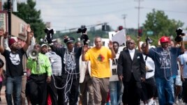 Protesters fill Florissant Road in downtown Ferguson, Mo. Monday, Aug. 11, 2014, marching along the closed street.