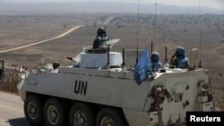 Para anggota pasukan penjaga perdamaian PBB mengendarai kendaraan lapis baja di Dataran Tinggi Golan yang dikuasai Israel, sebelum menyeberang ke Suriah (31/8). (Reuters/Baz Ratner)