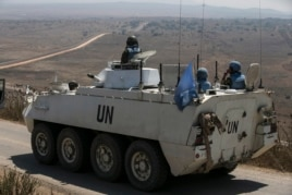 Members of the United Nations Disengagement Observer Force (UNDOF) ride on an armoured personnel carrier (APC) in the Israeli-occupied Golan Heights before crossing into Syria, Aug. 31, 2014.