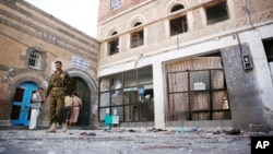 Houthi rebels inspect scene at al-Balili mosque after two suicide bombings during Eid al-Adha prayers in Sanaa, Yemen, Sept. 24, 2015.