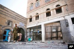 FILE - Shiite fighters, known as Houthis, inspect the the scene at the al-Balili mosque after two suicide bombings at the mosque during Eid al-Adha prayers in Sanaa, Yemen, Sept. 24, 2015.