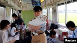 Seorang anggota staf organisasi menggendong seekor kucing di kafe kucing yang digelar di sebuah gerbong kereta di Jepang. Kampanye ini untuk meningkatkan kesadaran maraknya pemusnahan kucing di Jepang.