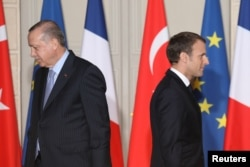 FILE - French President Emmanuel Macron (R) and his Turkish counterpart, Recep Tayyip Erdogan, walk past each other during a joint press conference at the Elysee Palace in Paris, France, Jan. 05, 2018.