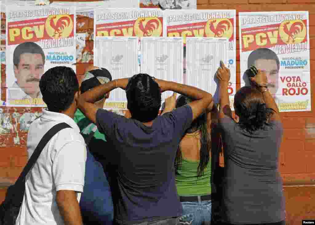 Venezolanos buscan sus números de mesa en los centros de votación para cumplir con su obligación durante la jornada electoral en Venezuela.