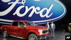 FILE - Ford Motor Co. Executive Chairman Bill Ford, left, and Chief Executive Mark Fields stand next to a Ford F-150 truck at the North American International Auto show, Jan. 9, 2017, in Detroit.