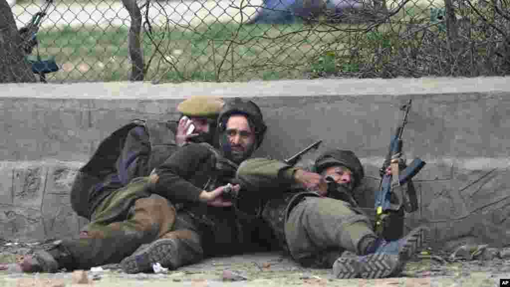 Indian police take cover during a gun battle in Srinagar, India, March 13, 2013.