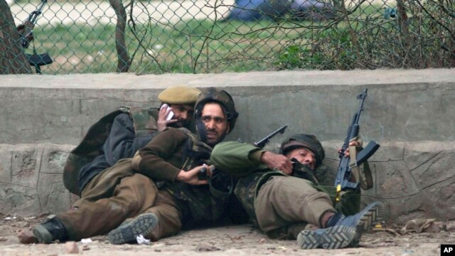 Indian police men take cover during a gun battle in Srinagar, India, Mar. 13, 2013.