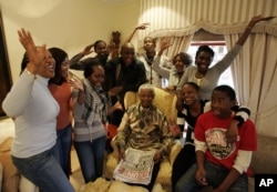 FILE - Former South Africa's President Nelson Mandela poses with his grandchildren, at his home in Qunu, South Africa.