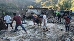 Des personnes pataugent dans une zone inondée à Dipayal Silgadhi, au Népal, le jeudi 21 octobre 2021.