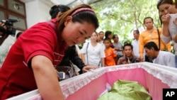 泰国的受害家庭围绕在四面佛爆炸事件中受害者的棺材旁。