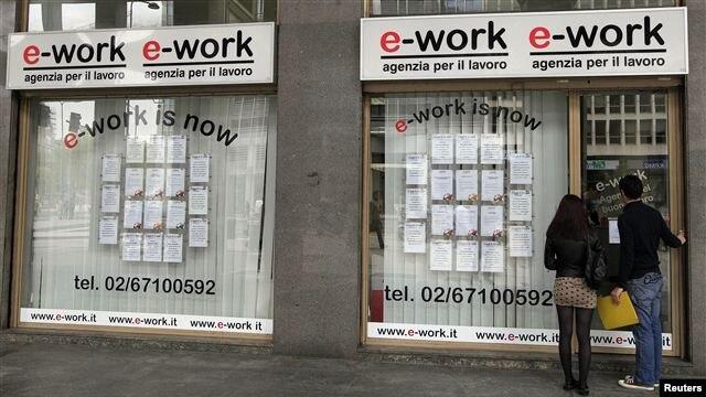 Una pareja de jóvenes italianos revisa las listas en una agencia de empleos en Milán.