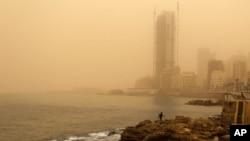 A man walks on the rocky coastal area along the Beirut coastline during a sandstorm in Beirut, Lebanon, Sept. 8, 2015.