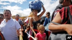 A woman carrying a bundle on her head wait in line to cross the border into Colombia through the Simon Bolivar bridge in San Antonio del Tachira, Venezuela, July 17, 2016.