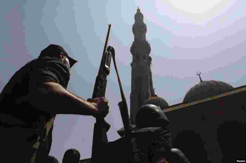 Armed Egyptian policeman moves into position in front of al-Fath mosque on Ramses Square in Cairo, August 17, 2013.