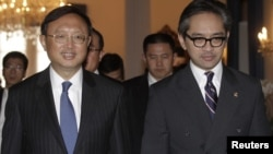 China's Foreign Minister Yang Jiechi (L) walks with his Indonesian counterpart Marty Natalegawa after a bilateral meeting at the Foreign Ministry office in Jakarta, August 10, 2012.