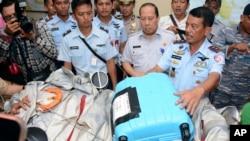 កងទ័ពអាកាសឥណ្ឌូនេស៊ី លោក Marshall Dwi Putranto, ខាងស្ដាំ, បង្ហាញបំណែកយន្តហោះនិងវ៉ាលីមួយដែលបានឃើញអណ្តែតលើទឹកនៅជិតកន្លែងដែលយន្តហោះរបស់ក្រុមហ៊ុនអាកាសចរណ៍ AirAsia ជើងហោះហើរលេខ 8501 បានបាត់ នៅឯមូលដ្ឋានទ័ពអាកាសនៅ Pangkalan Bun ភាគកណ្តាលកោះBorneo ប្រទេសឥណ្ឌូនេស៊ី កាលពីថ្ងៃទី៣០ ខែធ្នូ ឆ្នាំ២០១៤។