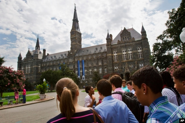 FILE - Prospective students tour Georgetown University's campus in Washington, July 10, 2013.