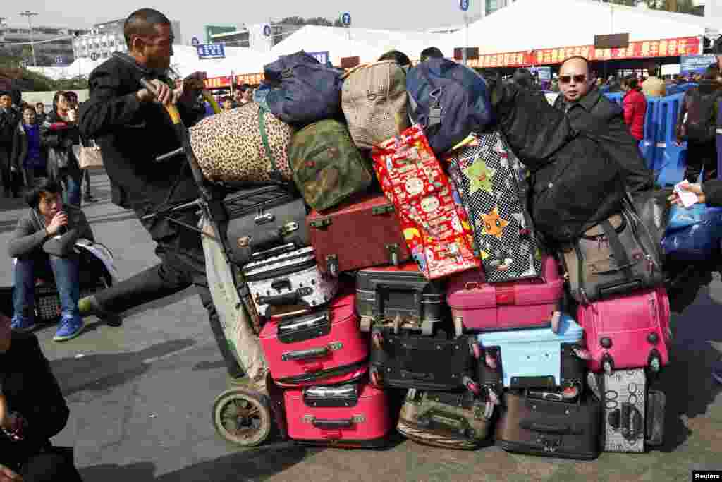 A man pushes a cart carrying passengers' luggage outside a railway station in Guangzhou, Guangdong province, China, Jan. 15, 2014, during the 40-day Spring Festival travel rush.