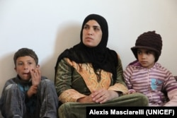 Seorang perempuan Suriah bersama dua anaknya di dalam apartemen mereka di Mafraq, sebelah utara Yordania. Suaminya tetap tinggal di Suriah. (Courtesy UNICEF/Alexis Masciarelly)