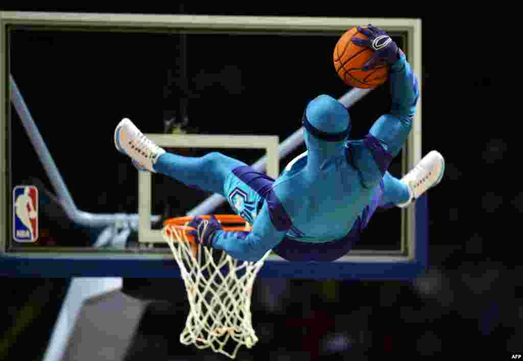 A man in a costume performs a stunt with a basketball before the 2015 NBA Global Games China pre-season basketball contest the Los Angeles Clippers play the Charlotte Hornets in Shanghai, Oct. 14, 2015.