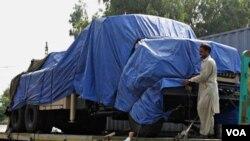 Truk-truk perbekalan NATO yang selamat dari serangan militan, masih tertahan di Khairabad, dekat Peshawar, Pakistan.
