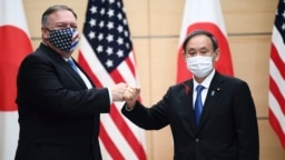 Japan's Prime Minister Yoshihide Suga, right, and U.S. Secretary of State Mike Pompeo, left, greet prior to their meeting at the prime minister's office in Tokyo, Tuesday, Oct. 6, 2020. (Charly Triballeau/Pool Photo via AP)