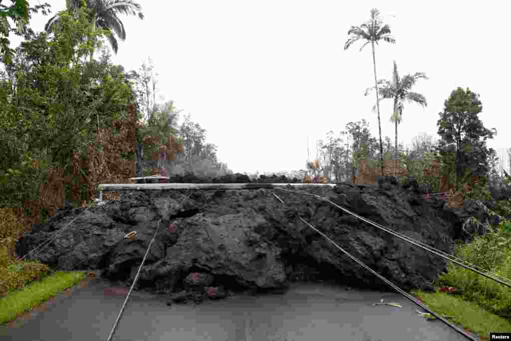 Lava and downed power lines block a road in the Leilani Estates subdivision during ongoing eruptions of the Kilauea Volcano, Hawaii, May 8, 2018.
