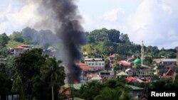 Asap mengepul dari gedung yang terbakar terlihat saat tentara pemerintah menyerang gerilyawan dari kelompok Maute, mengambil alih sebagian besar Kota Marawi, Filipina, 1 Juni 2017. (REUTERS/Romeo Ranoco)