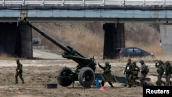 """South Korean soldiers of an artillery unit take part in an artillery drill with 155mm Towed Howitzers as part of the annual joint military exercise """"Foal Eagle"""" by the U.S. and South Korea, near the demilitarized zone (DMZ) which separates the two Korea, file photo."""