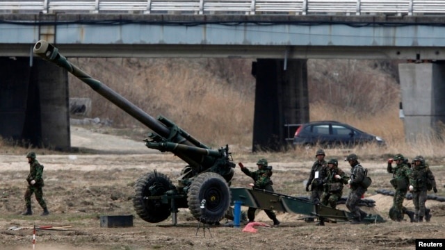 "South Korean soldiers of an artillery unit take part in an artillery drill with 155mm Towed Howitzers as part of the annual joint military exercise ""Foal Eagle"" by the U.S. and South Korea, near the demilitarized zone (DMZ)."