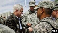 Menhan AS Robert Gates dan pasukan AS di Afghanistan. Penggunaan kekuatan militer menjadi opsi terakhir bagi pemerintahan Obama.
