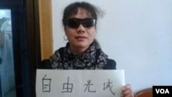 Bà Lưu Bình cầm tấm bảng với nội dung tỏ tinh thần đoàn kết với luật sư khiếm thị Trần Quang Thành