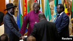 FILE - South Sudan's rebel leader Riek Machar (R) and South Sudan's President Salva Kiir (L) hold a priest's hands before signing an earlier peace agreement in Addis Ababa, May 9, 2014.