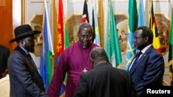 FILE - South Sudan's rebel leader Riek Machar (R) and South Sudan's President Salva Kiir (L) hold a priest's hands before signing an earlier peace agreement in Addis Ababa May 9, 2014.