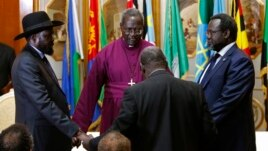 FILE - South Sudan's rebel leader Riek Machar (R) and South Sudan's President Salva Kiir (L) hold a priest's hands before signing an earlier peace agreement in Addis Ababa, Ethiopia, May 9, 2014.