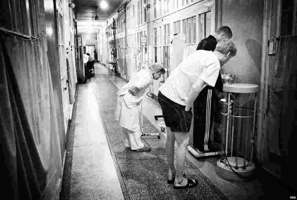Медсестра взвешивает больного, другой больной его подбадривает
