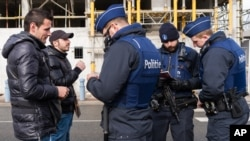 Cảnh sát kiểm tra hộ chiếu của hai người đàn ông tại biên giới Pháp-Bỉ, ngày 24/2/2016. Một trong những vấn đề trong chương trình họp hôm nay của EU là kế hoạch của Hungary đề ra hạn ngạch bắt buộc đối với từng nước trong việc tiếp nhận di dân.