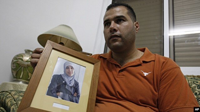 Palestinian Mohammed Tamimi holds a picture of his sister Ahlam Tamimi, held in an Israeli jail, during an interview in the West Bank city of Ramallah, October 16, 2011.