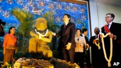 Cambodian Deputy Prime Minister Sok An, center, stands next to a 10th century Cambodian sandstone statue as the Director of the Cleveland Museum of Art William M. Griswold, right, holds a garland during a ceremony in Phnom Penh, Cambodia.