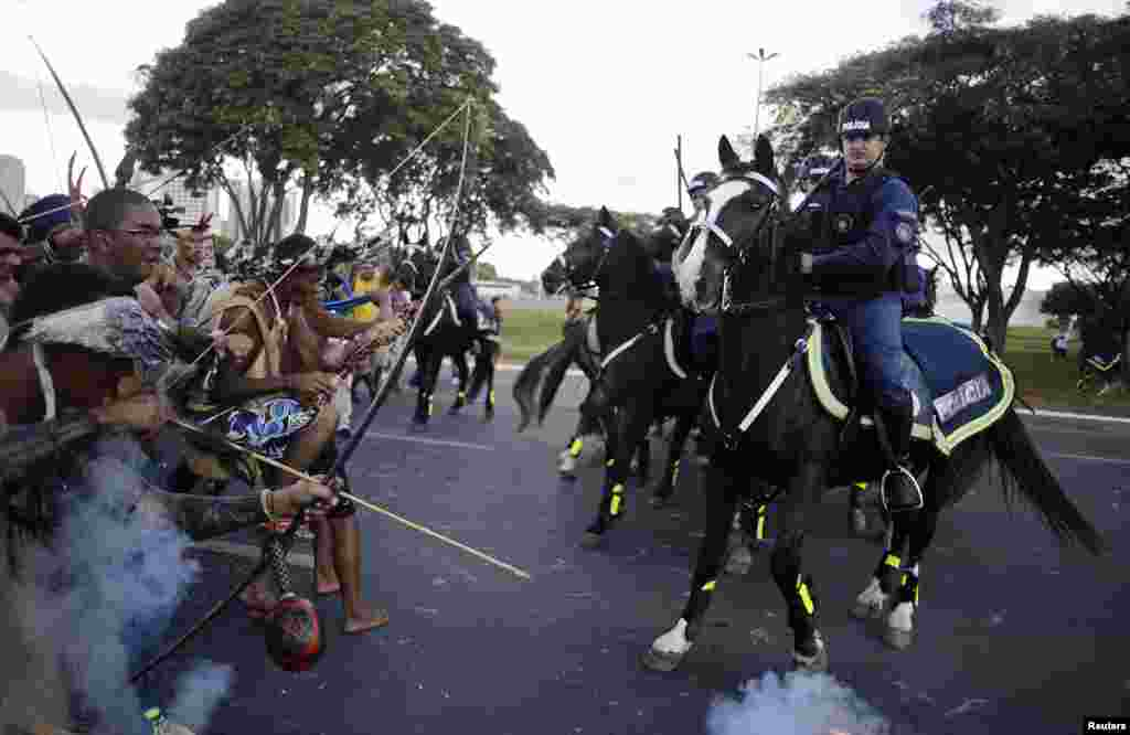Police use tear gas to impede native Brazilians from marching towards the Mane Garrincha soccer stadium during an anti-world cup demonstration in Brasilia, May 27, 2014.
